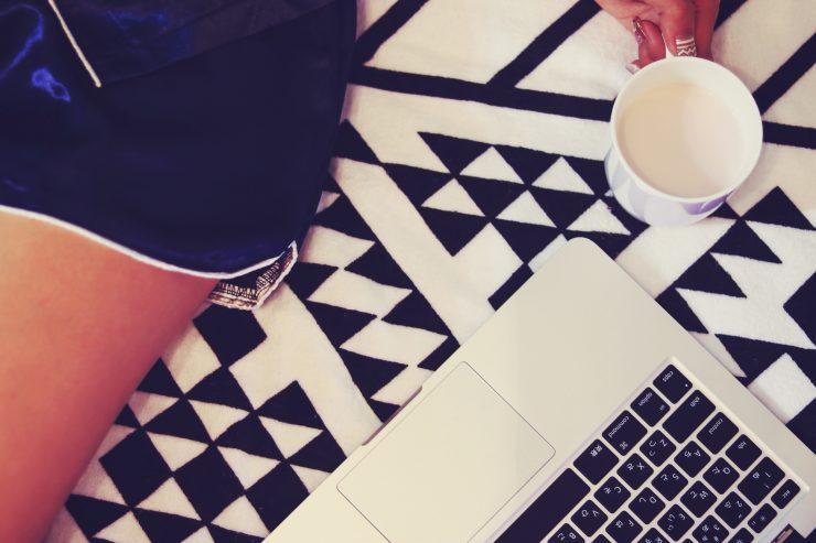 女の子がパソコン作業の合間にコーヒーブレイク